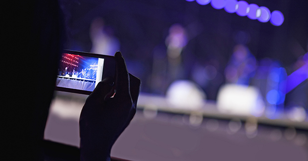 person taking a photo at a concert